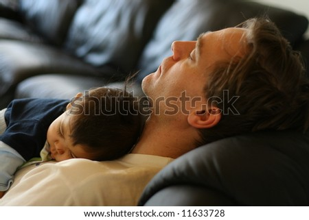 Baby asleep on his father's chest.;