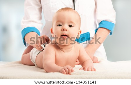 baby at the doctor pediatrician. doctor listens to the heart with a stethoscope - stock photo