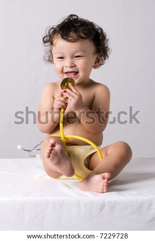 Baby at the doctor,playing with stethoscope. - stock photo