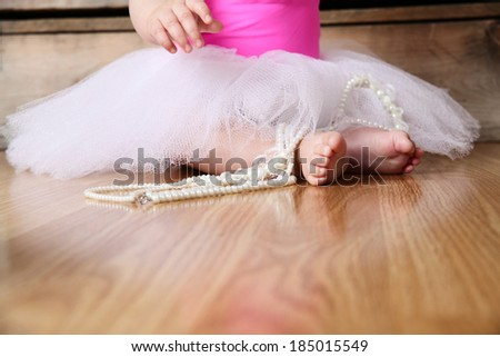 Baby ballerina feet on a wooden floor in white tutu - stock photo