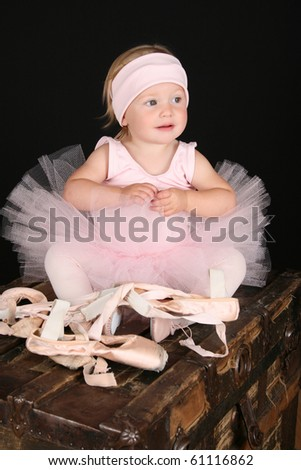 Baby ballerina sitting on an antique trunk - stock photo