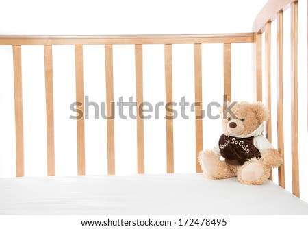 Baby bed with teddy bear for child on a white background - stock photo