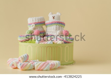 Baby birthday announcement. Infant booties with sweets and toy inside - stock photo