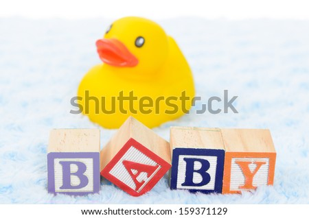 Baby blocks spelling baby and a rubber duck - stock photo