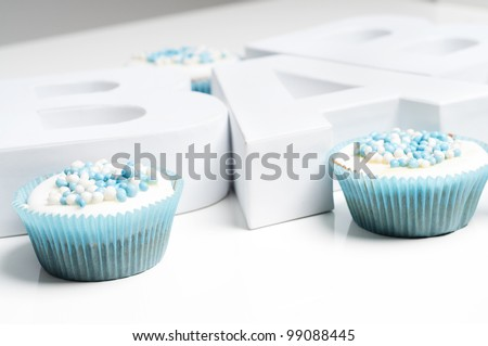 baby blue cupcakes with letters - stock photo