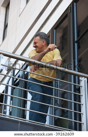 baby boomers  Iranian businessman with yellow shirt, standing in front of modern building - stock photo