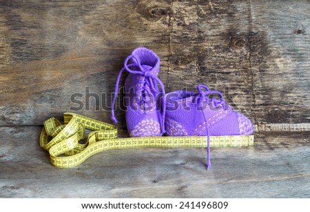 baby booties and measuring tape on the wooden background
