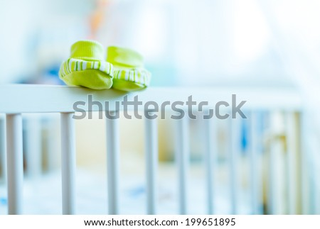 baby booties on a cot - stock photo