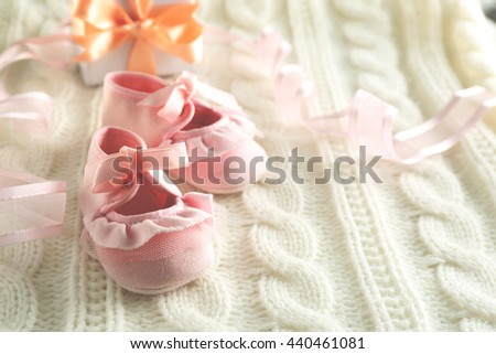 Baby booties on knitted plaid, closeup - stock photo