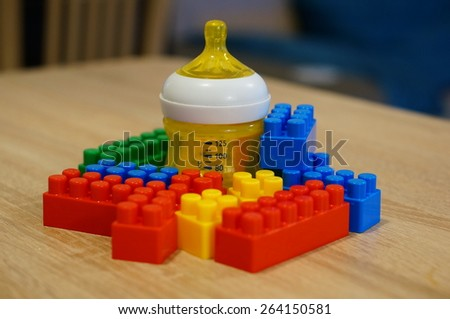 Baby bottle and toy blocks  - stock photo