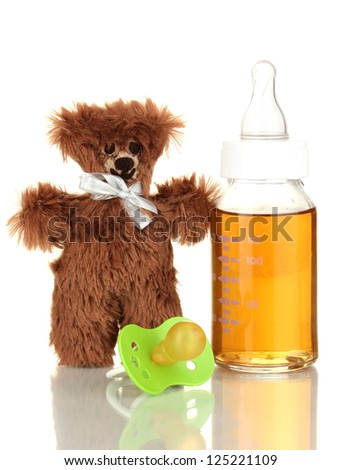 Baby bottle with fresh juice and teddy bear isolated on white - stock photo