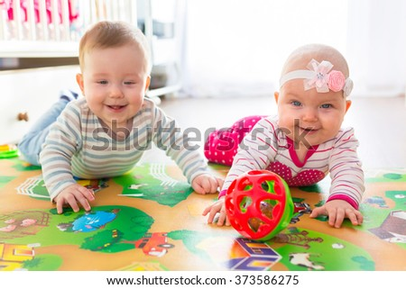 Baby boy and girl twins playing with the ball at home - stock photo