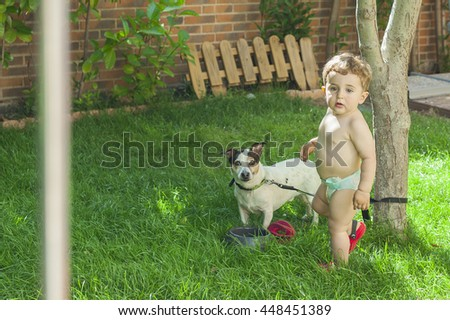Baby boy and his dog in the garden. Summertime