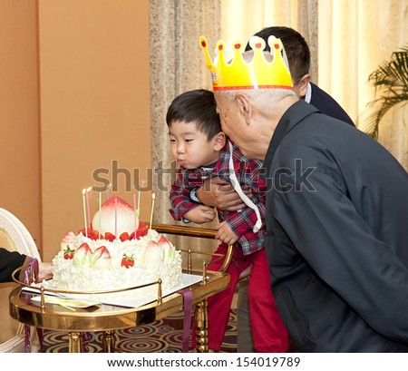 baby boy and his grandparents in the birthday party - stock photo