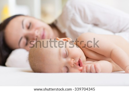 Baby boy and his mother relaxing in a white bedroom - stock photo