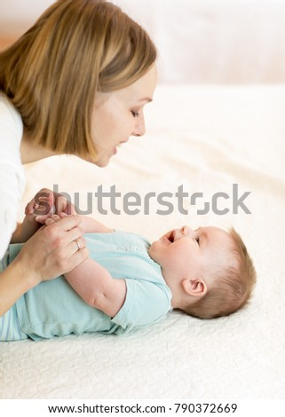 Baby boy and his mother relaxing in a white bedroom