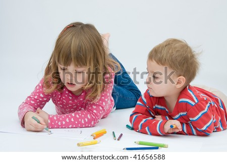 baby boy and little girl drawing on white paper - stock photo