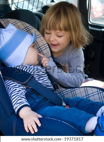 baby boy and little girl laughing in car backseat - stock photo