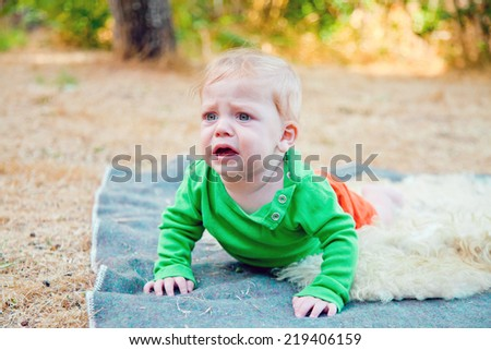 Baby boy bawling leaning on his palms while outdoors at sunset - stock photo