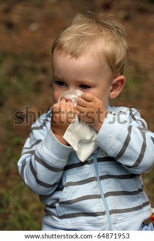 Baby boy blowing nose. Child with tissue. catarrh or allergy