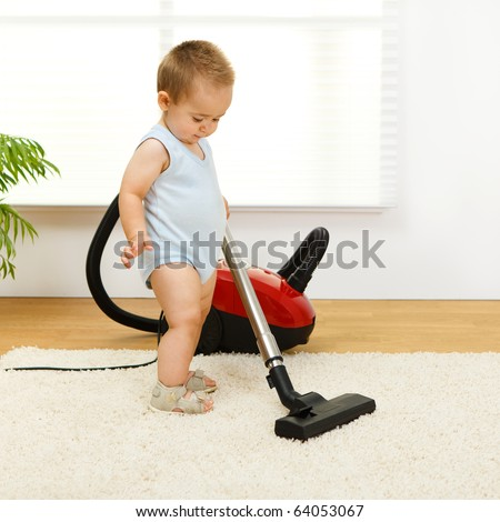 Baby boy cleaning the carpet with vacuum cleaner - stock photo