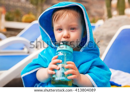 Baby boy covered by blue towel drinking juice at the pool - stock photo
