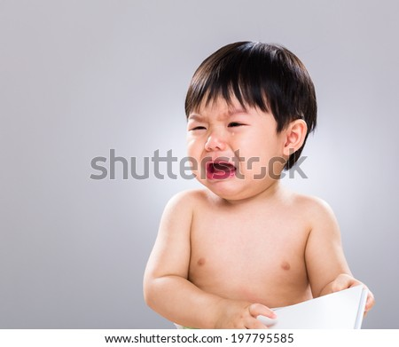 Baby boy cry with book - stock photo