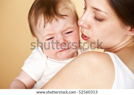 baby boy crying in mothers arm; closeup faces - stock photo