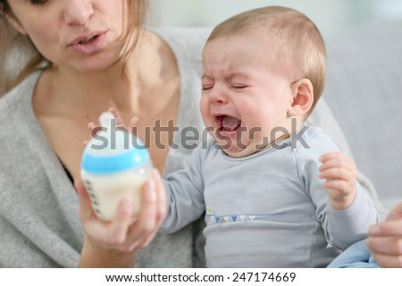 Baby boy crying to have food - stock photo