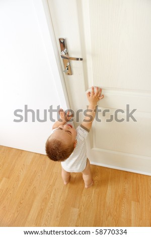 Baby boy crying, wants to reach the door handle. Conceptual view of being out of reach because of being too small for something - stock photo
