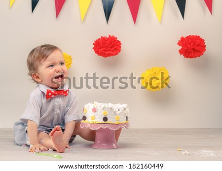 Baby boy crying while eating his birthday party cake. Smash the cake party - stock photo