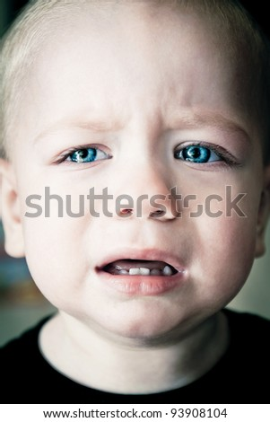 Baby boy crying with blue eyes full of tears close up portrait - stock photo