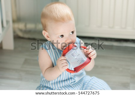 Baby boy drinking from baby cup and sitting on floor - stock photo