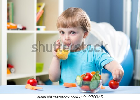 baby boy drinking juice at table in children room - stock photo