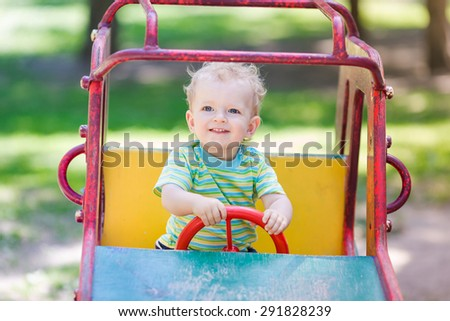 Baby boy driving a toy car at the playground outdoor - stock photo