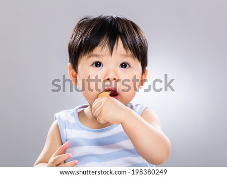 Baby boy eat biscuit - stock photo