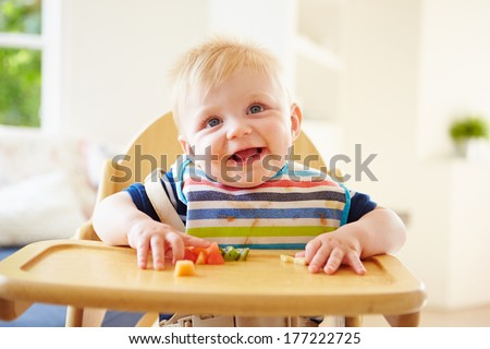 Baby Boy Eating Fruit In High Chair - stock photo