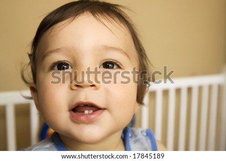 Baby boy - eleven months old - smiling while reaching out of his bed