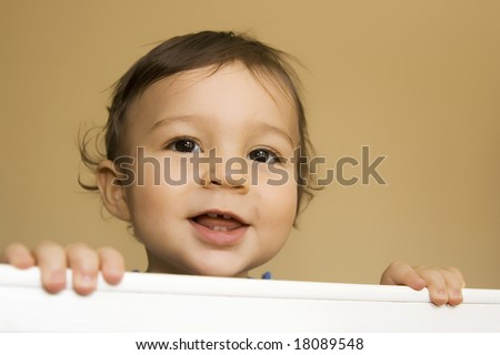 Baby boy - eleven months - smiling while reaching out of his bed holding the railing with both hands.