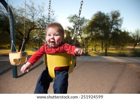 Baby Boy Enjoying Swing - stock photo