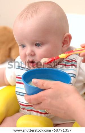 Baby boy feeding on sweet potatoes - stock photo