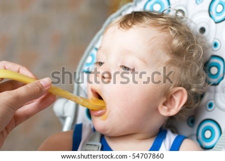 Baby boy feeding with a spoon at mum hand - stock photo