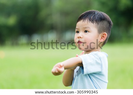 Baby boy feeling itchy and scratching his arm - stock photo