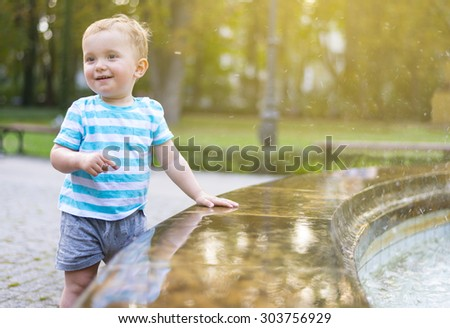 Baby boy having fun and playing with water at fountain - stock photo
