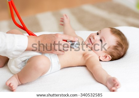 Baby boy having it's heartbeat checked by doctor pediatrist - stock photo