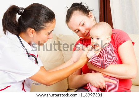 Baby boy held by his mother examined by pediatrician. - stock photo