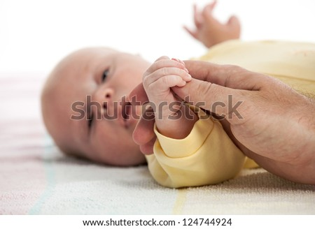 Baby boy holding father's hand, image with shallow depth of field