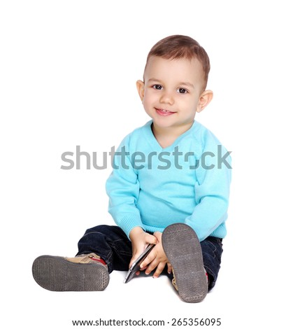 baby boy holding mobile phone in hands - stock photo