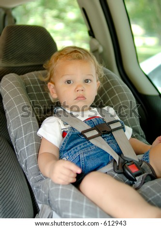 Baby boy in a car seat for safety. Focus = face. (12MP camera, Model Released.) - stock photo