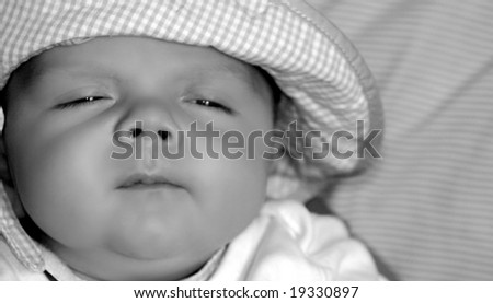 Baby boy in a hat, sleepy - stock photo